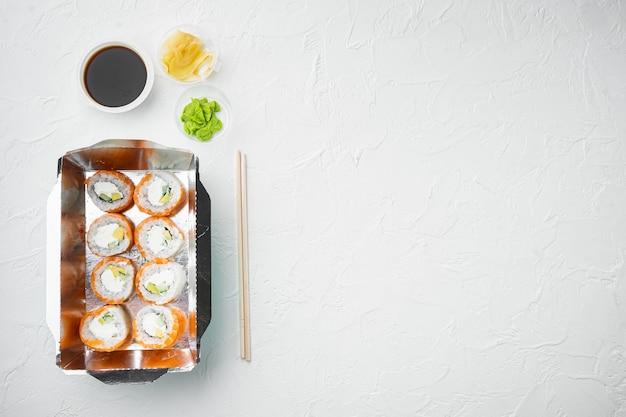 Saborosos rolos de sushi em caixinhas descartáveis montadas em pedra branca
