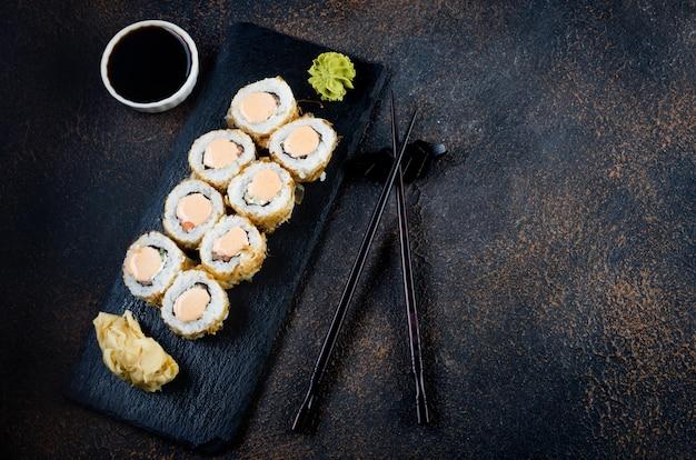 Saborosos rolos de sushi em prato de pedra com molhos, pauzinhos, gengibre e wasabi