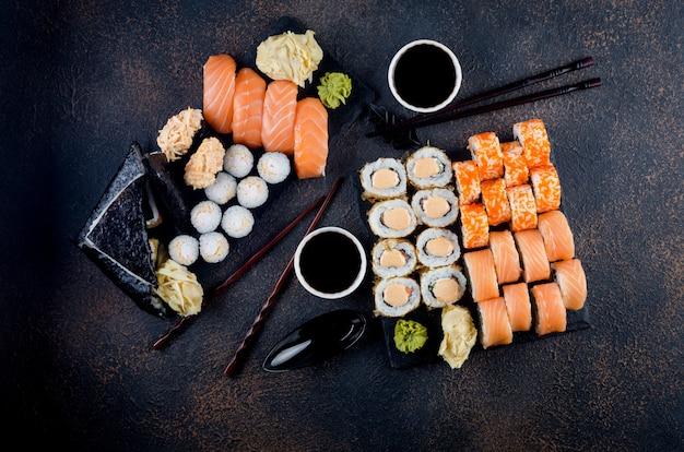 Saborosos rolos de sushi em prato de pedra com molhos