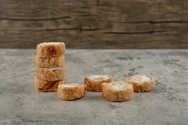 Saborosos rolos de sushi quentes colocados na mesa de pedra.