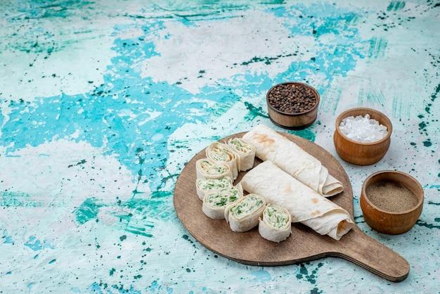 Saborosos rolos de vegetais inteiros e fatiados com verduras e temperos no piso azul brilhante, rolo de refeição alimentar