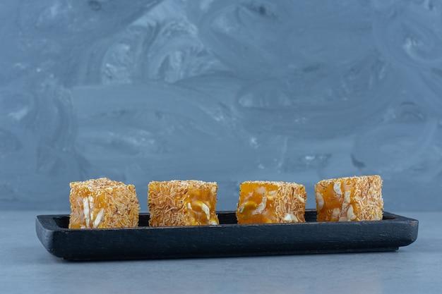 Saborosos sabores de delícias turcas em uma placa de madeira, no pano de prato, na mesa de mármore