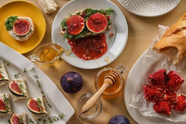 Saborosos sanduíches com figo maduro e mel na mesa de madeira