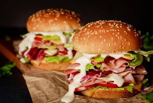 Saborosos sanduíches com legumes frescos e presunto na placa de madeira