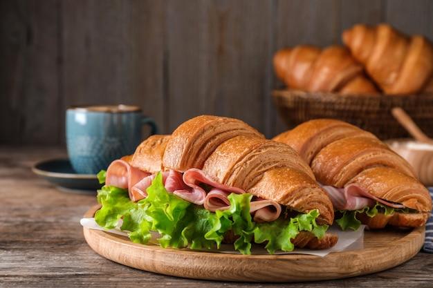 Saborosos sanduíches de croissant com presunto na mesa de madeira, closeup