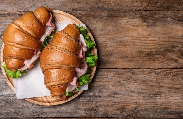 Saborosos sanduíches de croissant com presunto na mesa de madeira, vista superior. espaço para texto