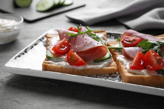Saborosos sanduíches de presunto servidos na mesa cinza, closeup