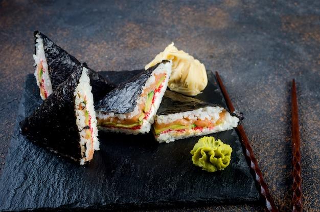 Saborosos sanduíches de sushi com salmão com molho de soja, gengibre, wasabi e pauzinhos