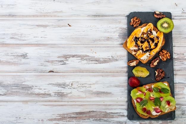 Saborosos sanduíches doces com banana, nozes e chocolate, kiwi, morangos e hortelã na mesa de madeira