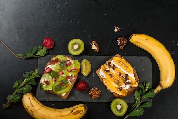 Saborosos sanduíches doces com bananas, nozes e chocolate, kiwi, morangos e hortelã no fundo preto