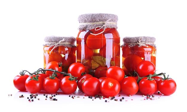 Saborosos tomates enlatados e frescos, em branco