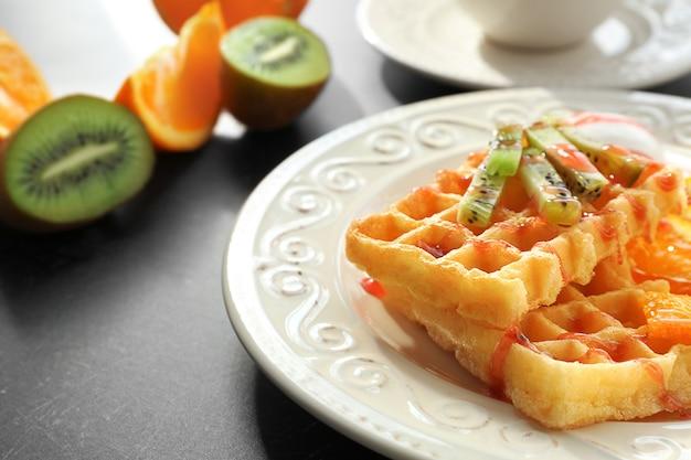 Saborosos waffles com frutas deliciosas, sorvete e calda em prato branco