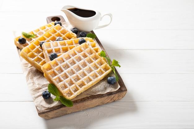 Saborosos waffles com geléia e mirtilos. no fundo de madeira