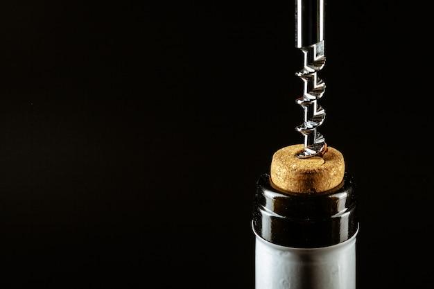 Saca-rolhas aparafusada na rolha na garrafa de vinho