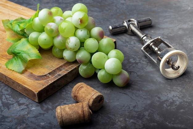Saca-rolhas com uvas verdes em uma placa de madeira