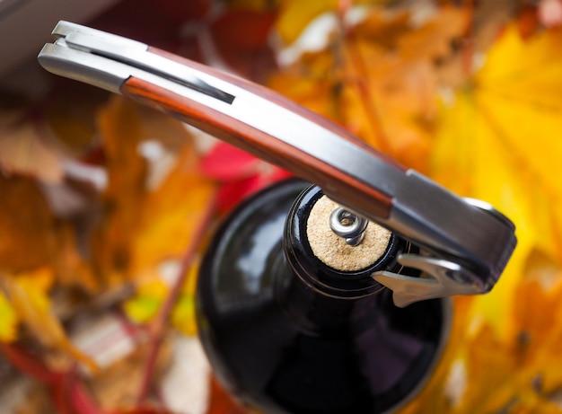 Saca-rolhas e garrafa de vinho tinto. abrindo uma garrafa de vinho. fechar-se.