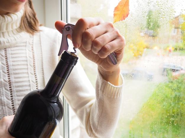Saca-rolhas e garrafa de vinho tinto. abrindo uma garrafa de vinho.