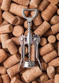 Saca-rolhas moderno de aço em cima de várias rolhas de vinho. macro