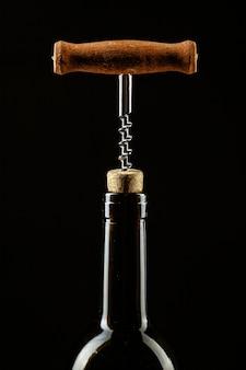 Saca-rolhas parafusado na rolha na garrafa de vinho