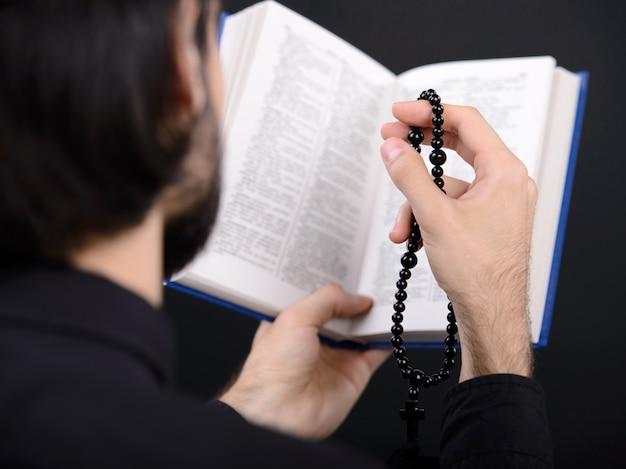 Sacerdote com a bíblia sagrada. retrato, de, padre, leitura, bíblia