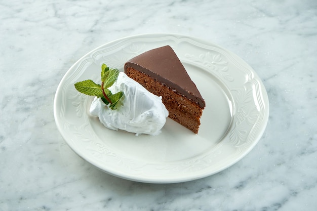 Sachertorte vienense clássico servido em um prato branco sobre uma mesa de mármore. bolo de chocolate sacher austríaco