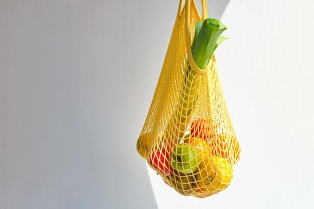 Saco amarelo com mistura de frutas e vegetais