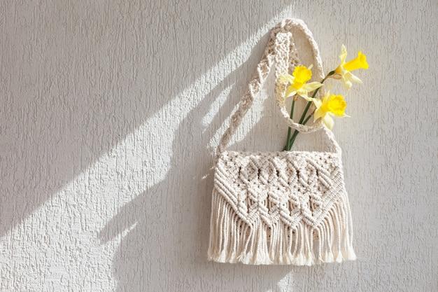 Saco artesanal de macramê com flores na parede clara
