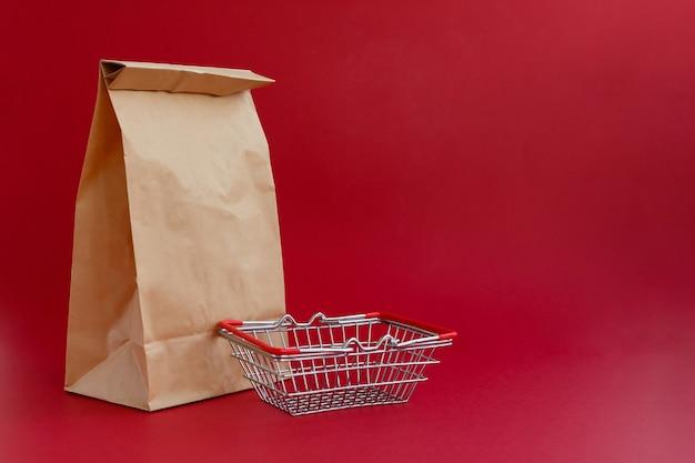Saco artesanal de papel marrom para compras em fundo vermelho e uma pequena cesta de supermercado