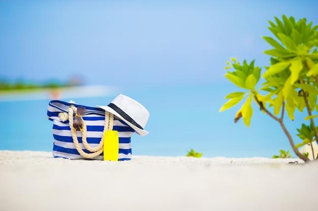 Saco azul, chapéu de palha, óculos escuros e protetor solar garrafa na praia branca