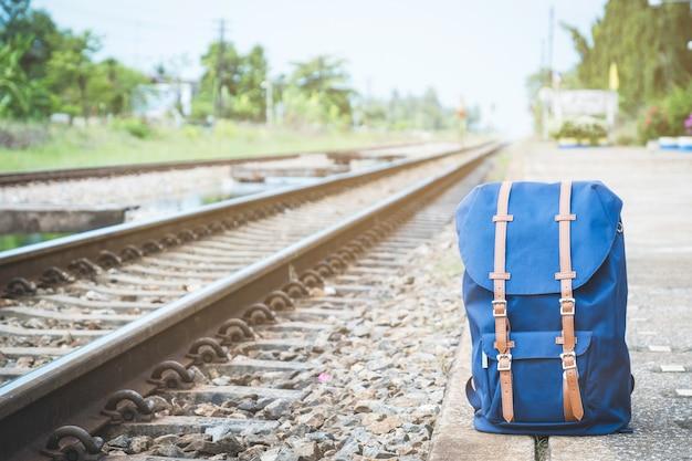 Saco azul na plataforma da estação de trem perto da estrada de ferro.