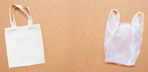 Saco branco da tela com o saco de plástico branco no fundo da madeira compensada.