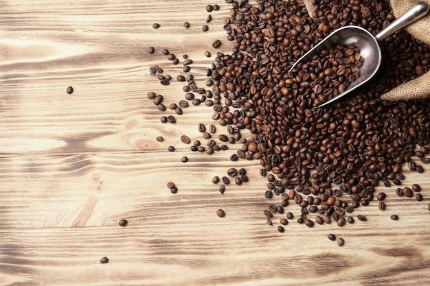 Saco, colher e grãos de café na superfície de madeira