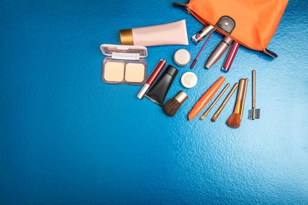Saco colorido aberto com acessórios e cosméticos