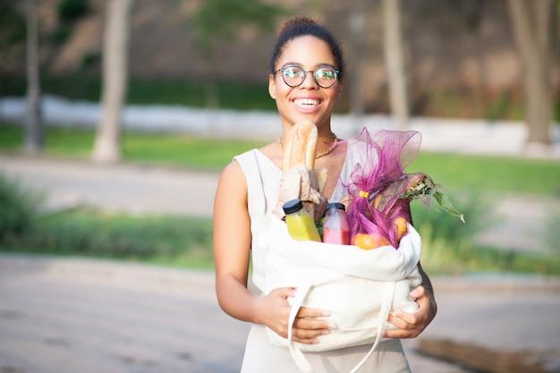 Saco com alimentos. mulher alegre de óculos vai voltar para casa e sacola com alimentos