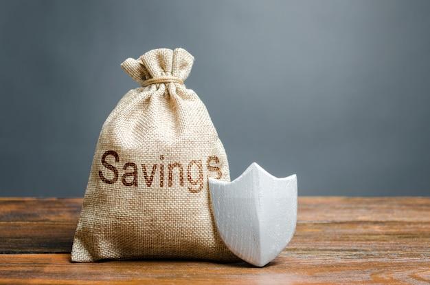 Saco com as palavras poupança e escudo de proteção. conceito de proteção de poupança e dinheiro