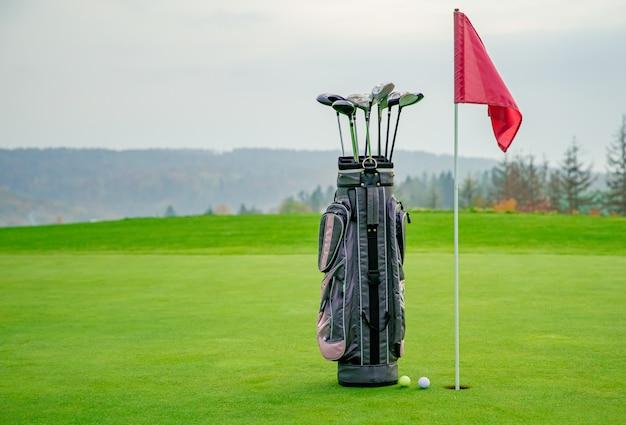 Saco com equipamento de golfe em campo verde