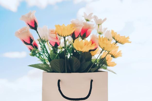 Saco com flores da primavera e fundo do céu ensolarado