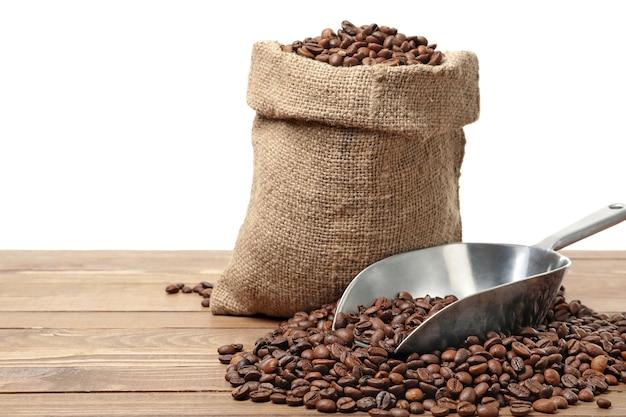 Saco com grãos de café e colher na mesa