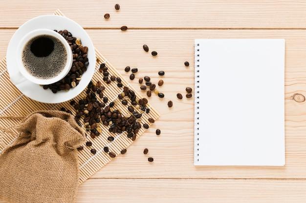 Saco com grãos de café e maquete de caderno