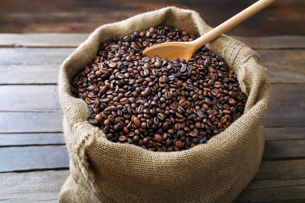Saco com grãos de café torrados com colher na mesa de madeira