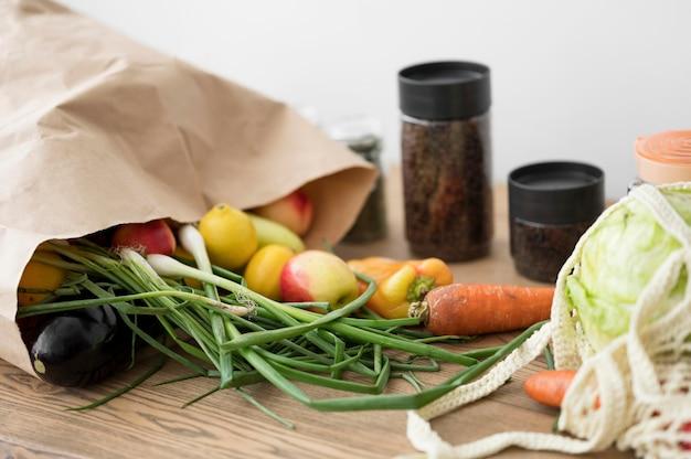Saco com legumes e frutas na mesa de madeira