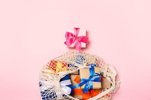 Saco com presentes em uma superfície rosa. conceito de presentes para a família, entes queridos, natal, dia dos namorados. vista plana, vista superior