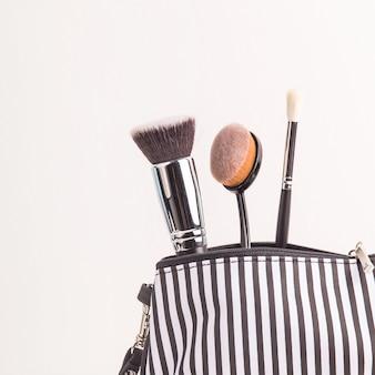 Saco cosmético preto e branco entre pincéis de maquiagem em um fundo branco