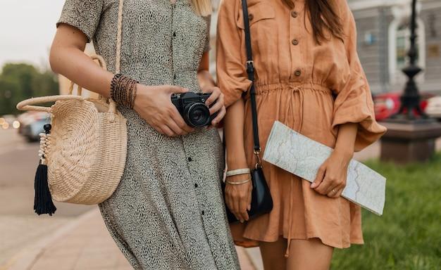 Saco de acessórios de detalhes de mãos de close-up, mapa, câmera fotográfica de mulheres elegantes viajando juntas vestidas com roupas da moda de primavera, estilo de rua