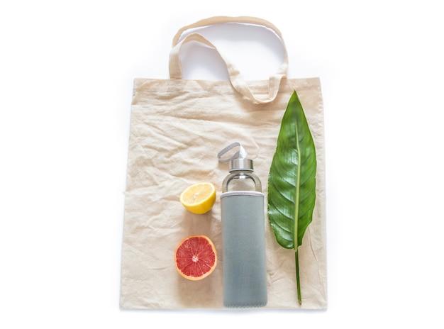 Saco de algodão com garrafa de água frutas limões crus, folha verde na parede branca plana leigos. zero resíduos reutilizáveis materiais ecológicos sem plástico