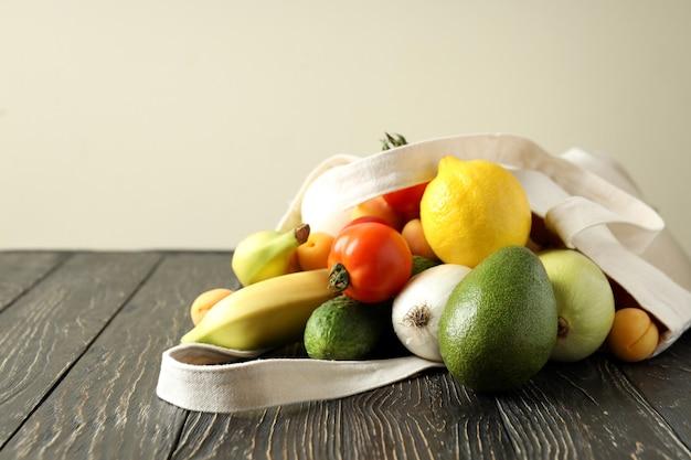 Saco de algodão com legumes e frutas na mesa de madeira