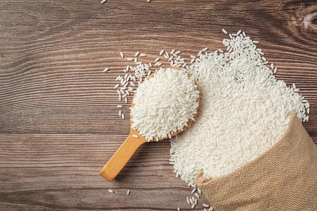 Saco de arroz branco e colher de pau colocados no chão de madeira