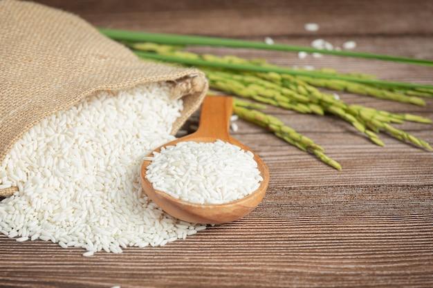 Saco de arroz com arroz na colher de pau e planta de arroz