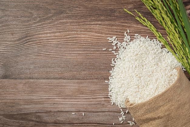 Saco de arroz com planta de arroz colocado no chão de madeira