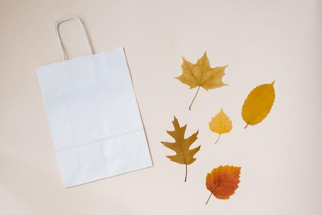 Saco de artesanato branco para suas compras com folhas de outono em um fundo de papel bege. conceito de outono. espaço de cópia da vista superior